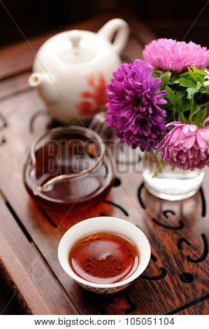 Small Bouquet Of Purple And Pink Asters And Black Tea In Chinese Tradition On Carved Tea Tray