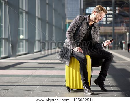 Smiling Man Resting At Airport With Mobile Phone