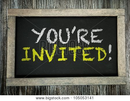 You're Invited! written on chalkboard