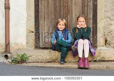 Outdoor portrait of two adorable kids wearing schoolwear