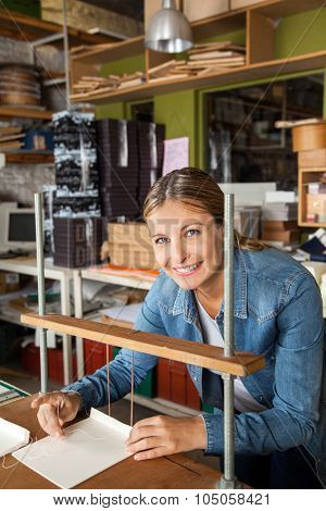 Portrait of confident female worker smiling while binding papers in factory