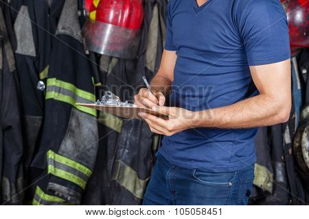 Midsection of firefighter writing on clipboard at fire station