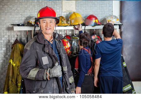 Portrait of smiling mature fireman at fire station with team in background