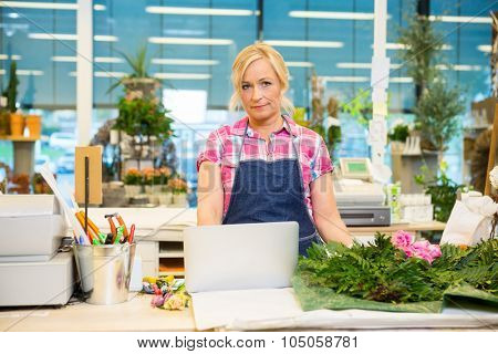 Portrait of mature female florist using laptop at counter in flower shop