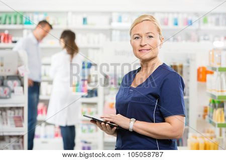 Portrait of confident assistant holding tablet computer while pharmacist and customer standing in background at pharmacy