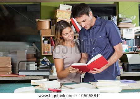 Smiling male and female workers looking at book in paper factory