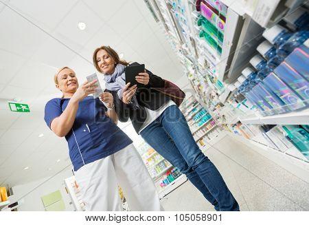Tilt image of smiling female chemist explaining product details to customer in pharmacy