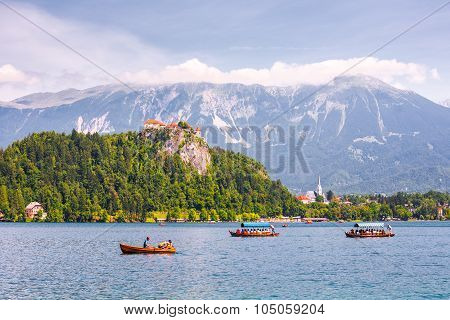 Bled Castle On A Precipice Overlooking Bled Lake With Tourists And Boats