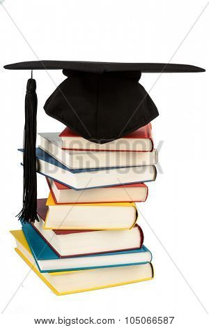 a mortar board on a pile of books, symbolic photograph of education and competence