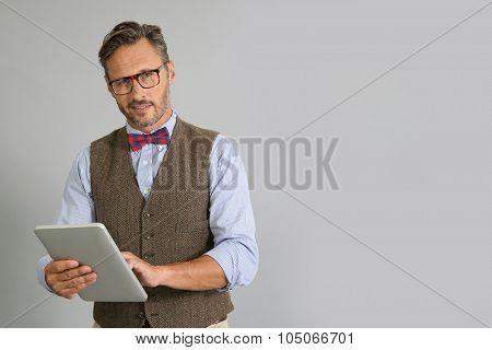 Stylish guy using digital tablet on grey background