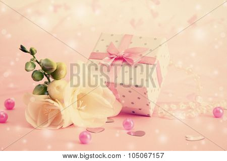 Beautiful little gift box and freesia flower on pink background