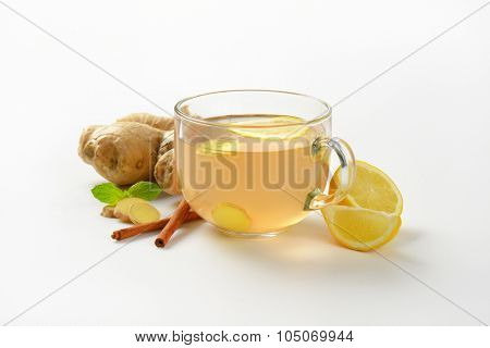 cup of ginger tea with lemon, fresh ginger and cinnamon on white background