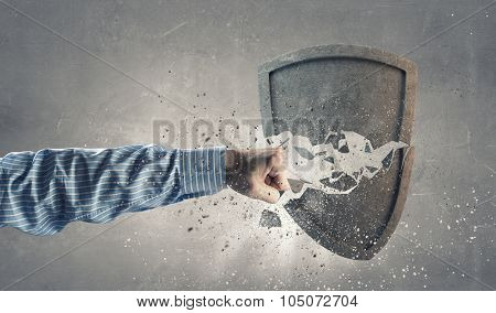 Conceptual image with hand breaking old stone shield