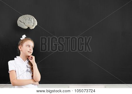 Cute thoughtful school girl and brain above her head