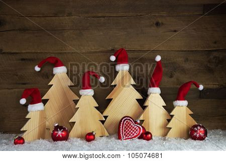 Romantic wooden christmas background with red santa hats and crafted trees.