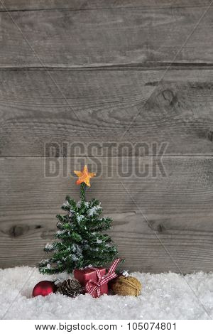 Wooden old country style background with a green christmas tree and a red gift box with checked ribbon.