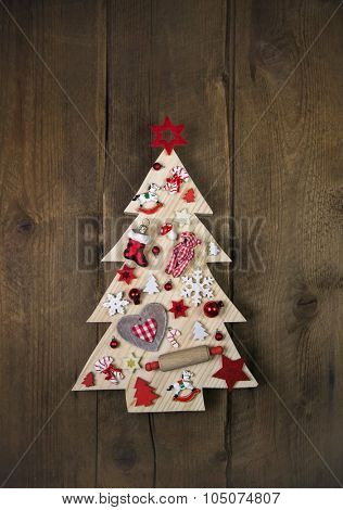 Handmade and carved christmas tree on dark brown wooden background with red white checkered decoration.