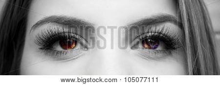 Black and white close-up image of female eyes with nebula colors and fake eyelashes