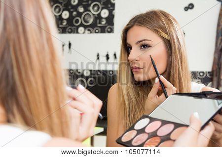 Teenage girl applying makeup on eyes