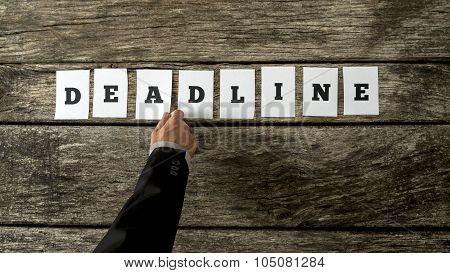 Overhead View Of Businessman Or Professor Hand Assembling A Deadline Sign
