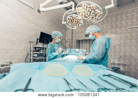 Surgeons team working with Monitoring of patient in surgical operating room.breast augmentation.