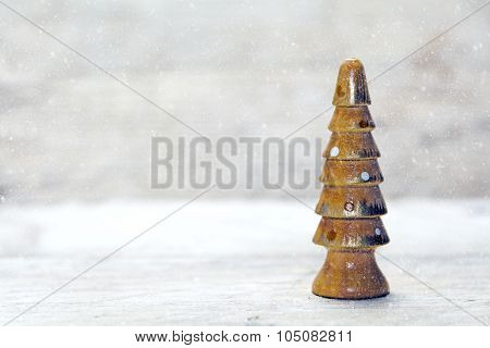 Small Wooden Christmas Tree Against A Snowy Gray Background