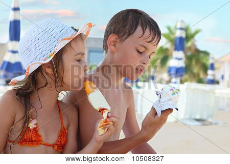 Brother and little sister eating ice cream after bathing.