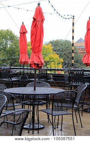 Rainy day with outdoor umbrellas and empty tables