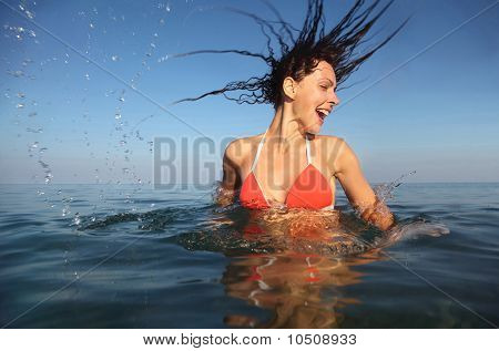 beautiful woman wearing red bathing suit spinning in sea.