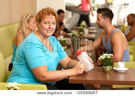 Young fat woman looking desperate, sitting at gym coffee table holding water bottle in hand.
