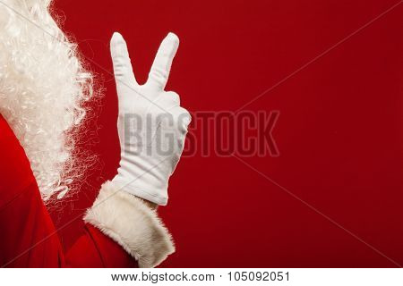 Photo of Santa Claus gloved hand in pointing gesture. fingers
