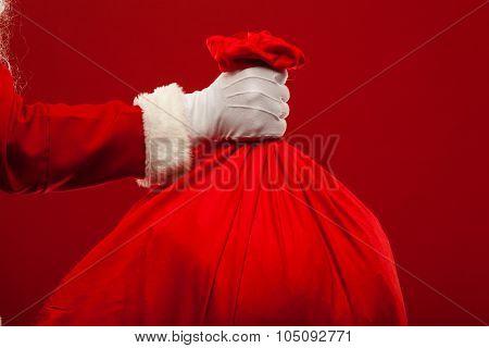 santa claus with big bag on shoulder glasses  red background