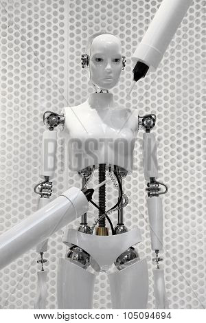 Futuristic white robot woman being made by the machines