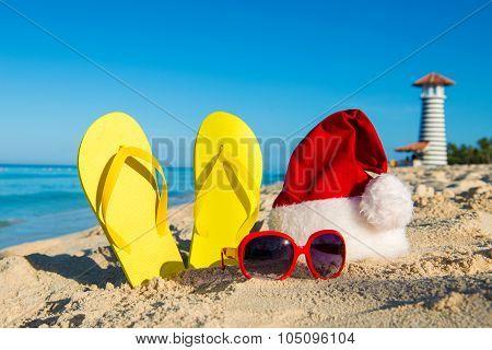 New Year Celebration At The Seaside. Santa Hat, Sandals, Sunglasses - Christmas Holiday At Sea.