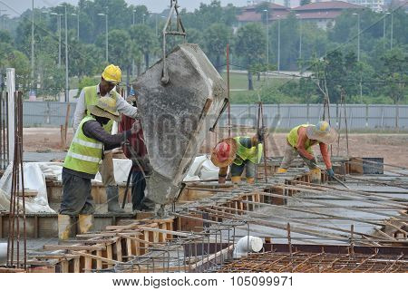 Group of construction workers casting floor beam