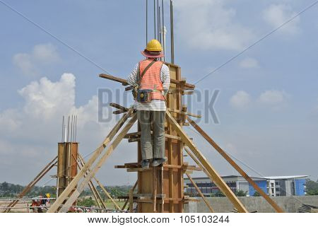 Construction workers fabricating column timber formwork