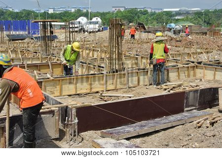 Construction workers fabricate ground beam formwork
