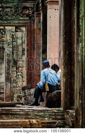 Two man sitting between stone doors