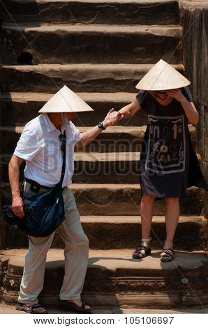 Two persons with hat climbing down stairs