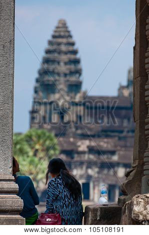 Girl sitting in front of Angkor Wat
