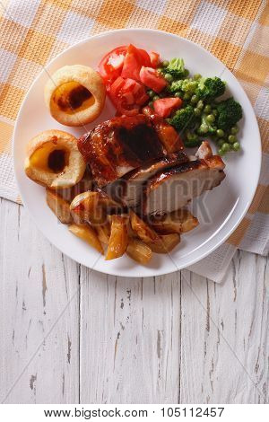 Pork With Potatoes, Vegetables And Yorkshire Pudding Vertical Top View