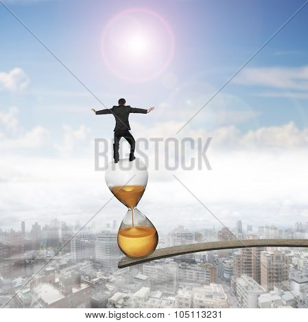 Businessman Balancing Hourglass On Edge Of Wooden Plank
