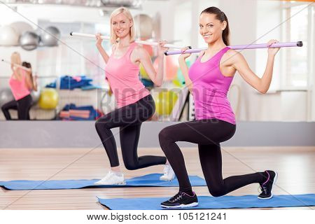 Cheerful slim girls are training with equipment