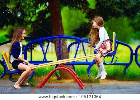 Cute Girls Having Fun On Seesaw At Playground