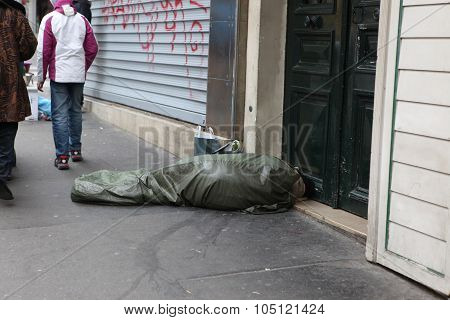Paris - May 1 : Homeless Man Curled Up Under A Plastic Tarpaulin, Asleep On The Street, May 1, 2013