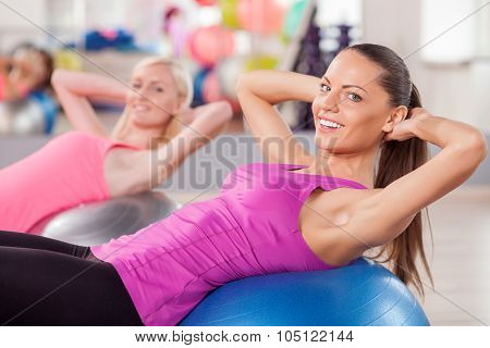 Pretty young women are exercising in fitness center
