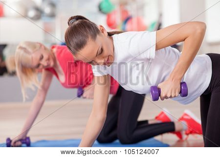 Pretty slim girls are exercising with dumbbells