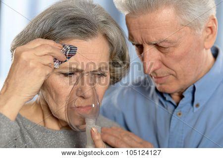 Elderly  couple making inhalation