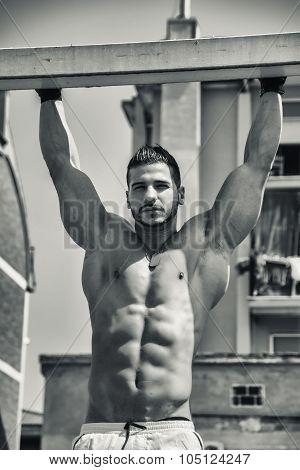 Young muscular man shirtless outdoors