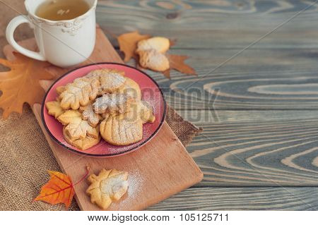 Delicious homemade cookies in the form of a maple leaf, oak leaves and acorns on wooden background.